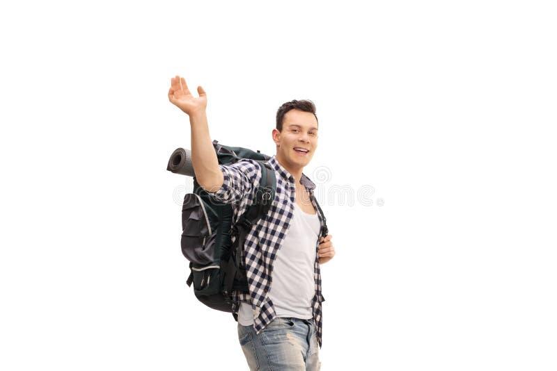 Männlicher Wanderer mit dem Rucksack, der an der Kamera wellenartig bewegt lizenzfreie stockfotos