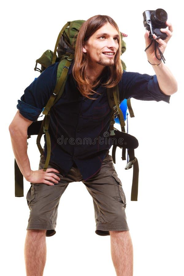 Männlicher Wanderer mit der Rucksack- und Kameraaufstellung lokalisiert stockbilder