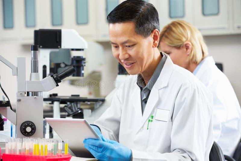 Männlicher Wissenschaftler, der Tablette-Computer im Labor verwendet stockfoto