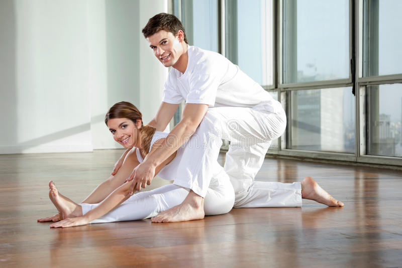 Männlicher Yoga-Lehrer Assisting Woman lizenzfreie stockbilder