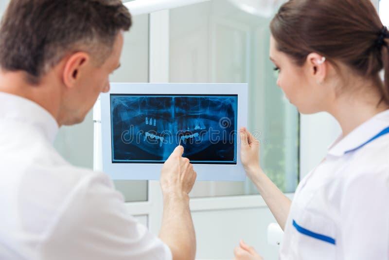 Männlicher Zahnarzt, der etwas auf dem Computermonitor zeigt stockfoto