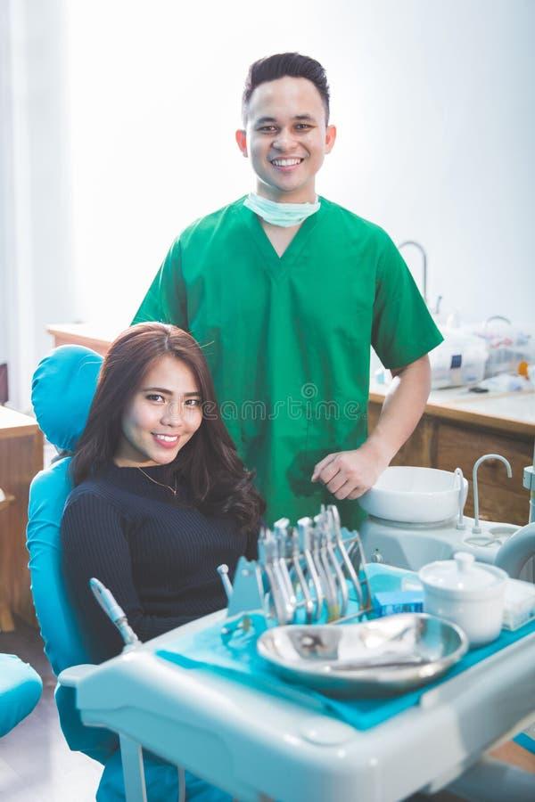 Männlicher Zahnarzt und Werkzeuge über der Klinik des Ärztlichen Diensts, die um sich kümmert lizenzfreies stockbild