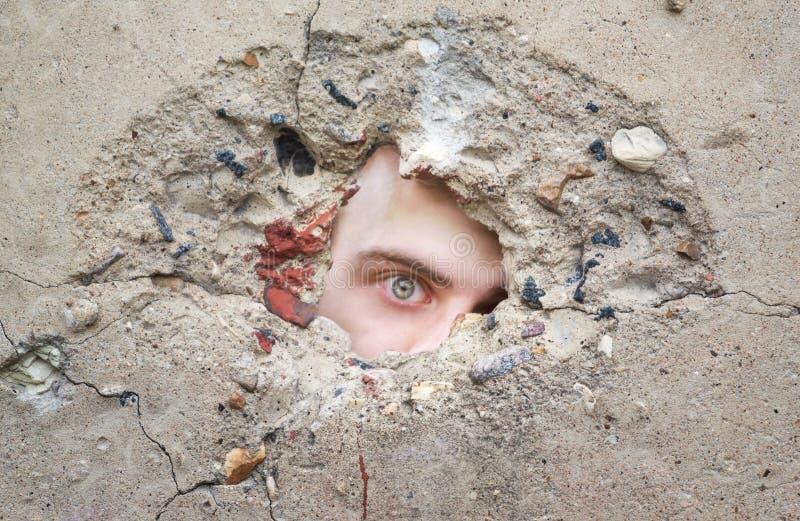 Männliches Auge schaut durch ein Loch in der Betonmauer und sucht nach Informationen, Spion lizenzfreies stockbild