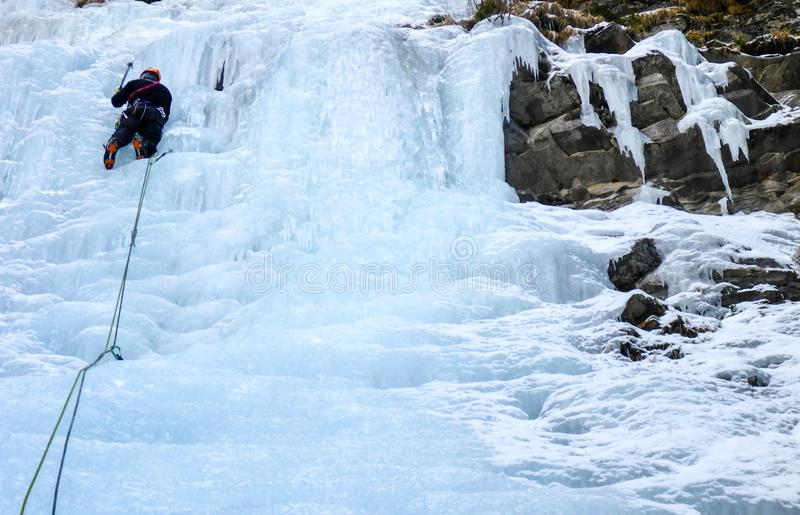 Männliches Bergführerführungseis, das einen gefrorenen Wasserfall im tiefen Winter in den Alpen von der Schweiz klettert lizenzfreie stockfotos