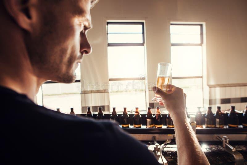 Männliches Brauerprüfungs-Handwerksbier an der Brauereifabrik stockfoto