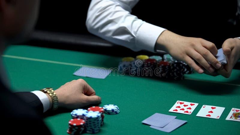 Männliches Croupier, welches die Karten für Geschäftsmannpokerspieler, hoffend für gute Hand behandelt lizenzfreie stockbilder