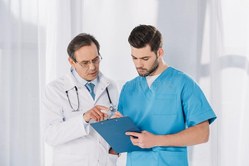 männliches Doktor- und Krankenschwesterschauen lizenzfreie stockbilder