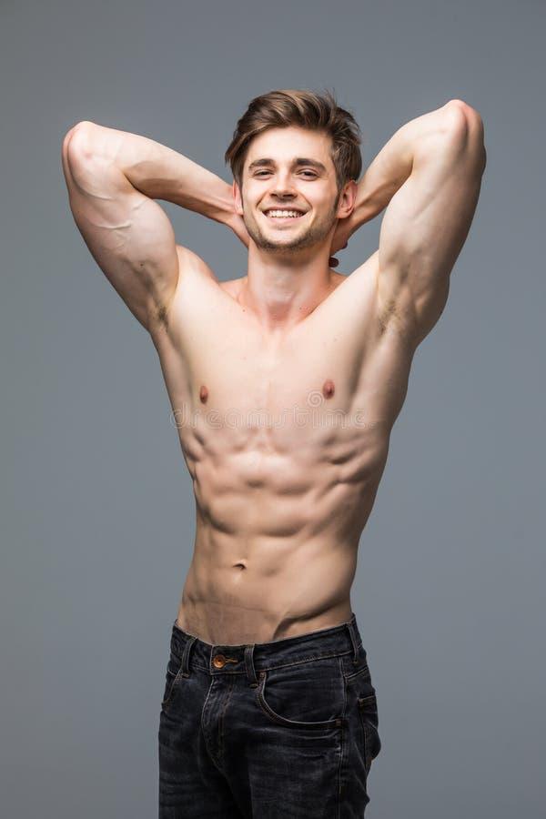 Männliches Eignungsmodell mit hübschem heißem jungem Mann des sexy Porträts des muskulösen Körpers mit dem Sitz athletisch lizenzfreies stockfoto