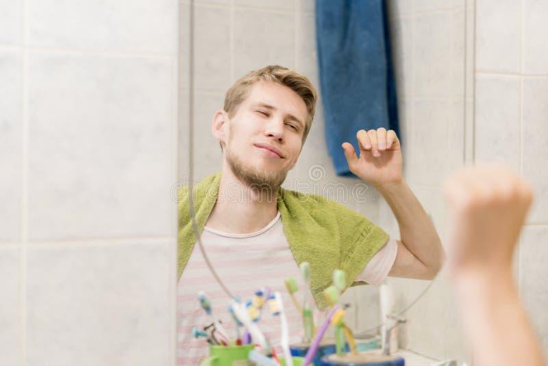 Männliches erwachsenes Ausdehnen vor Spiegel im Badezimmer am Morgen stockfotos