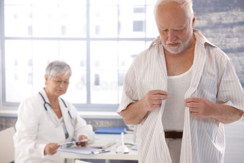 Männliches geduldiges Ausziehen am Raum des Doktors lizenzfreies stockbild