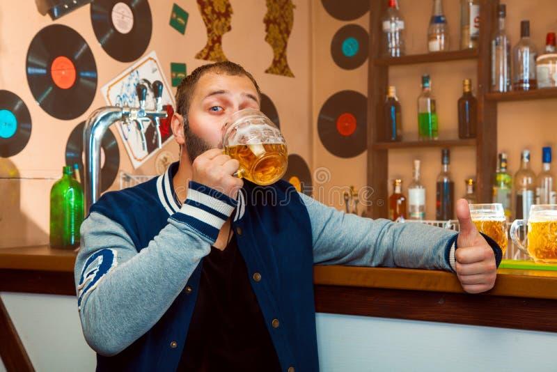 Männliches Getränkbier in der Bar lizenzfreie stockbilder