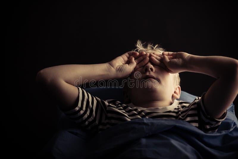 Männliches Kinderreibung mustert beim Legen in Bett stockfoto
