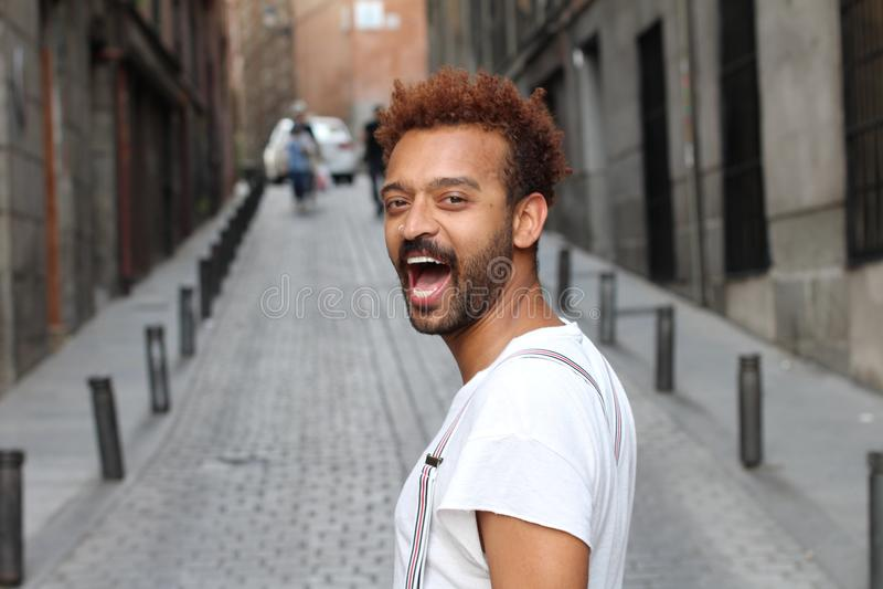 Männliches Modell, das heraus draußen lautes lacht stockfoto