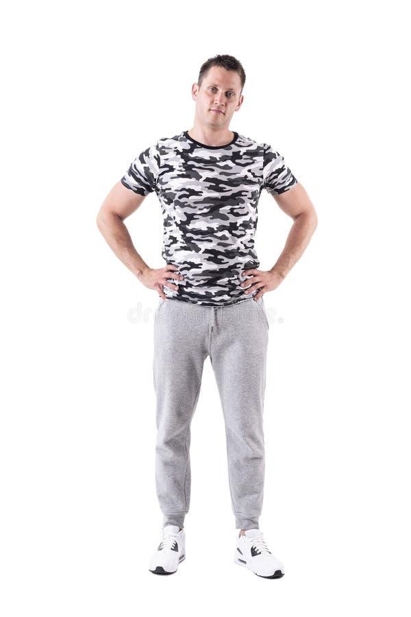 Männliches Modell der entspannten jungen Eignung, das mit den Händen auf Hüften mit gespanntem Kopf aufwirft stockfotografie
