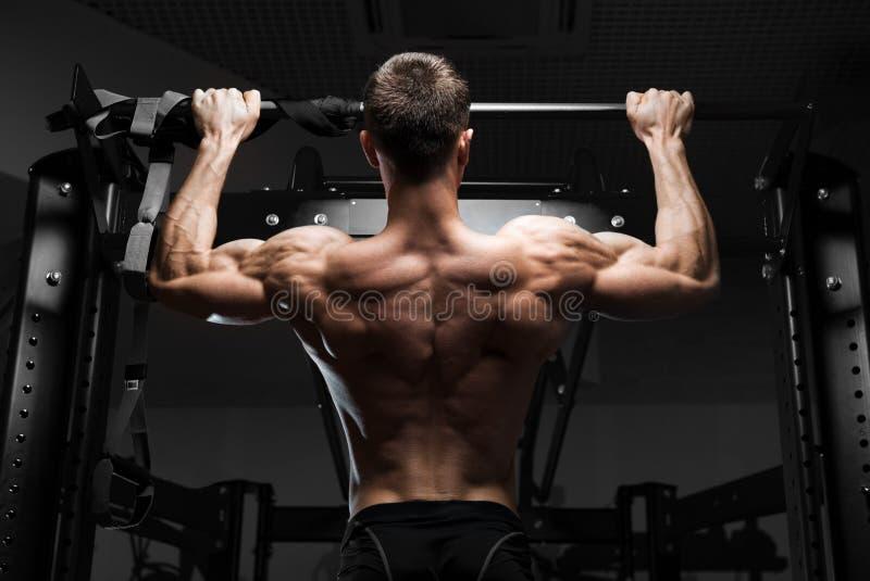 Männliches Modell der muskulösen Eignung des Athleten, das auf horizontaler Stange hochzieht lizenzfreies stockbild