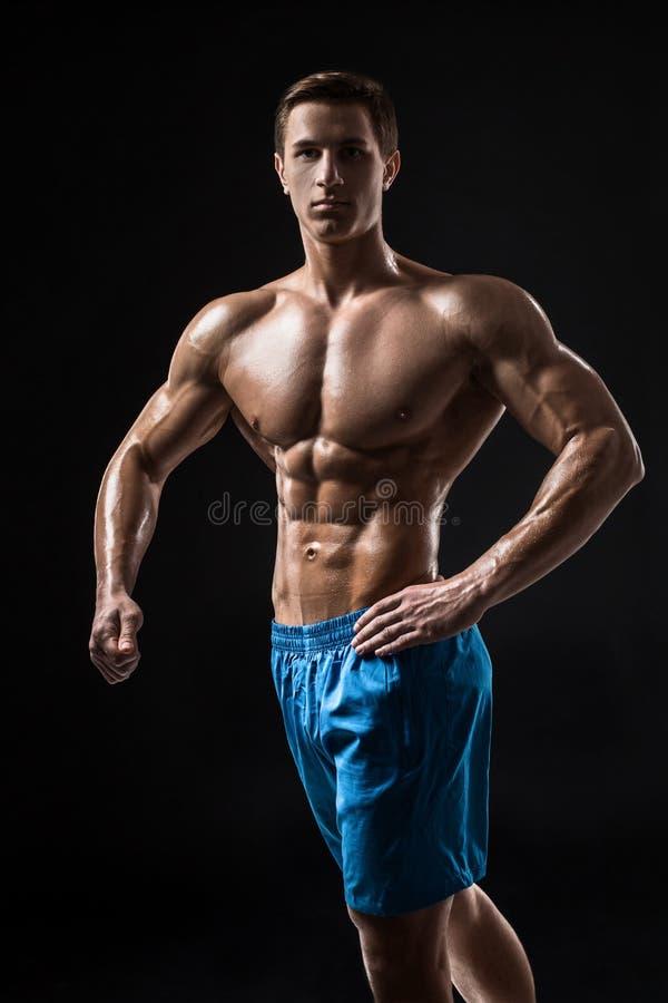 Männliches Modell der muskulösen und geeigneten jungen Bodybuildereignung, das über schwarzem Hintergrund aufwirft lizenzfreie stockbilder