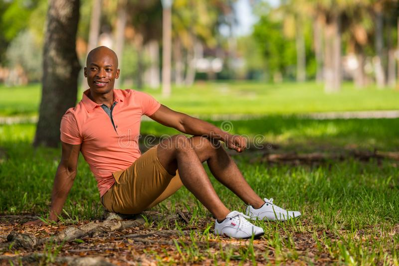 Männliches Modell des attraktiven jungen Afroamerikaners, das im Park flüchtig blickt über Schulter sitzt lizenzfreie stockbilder