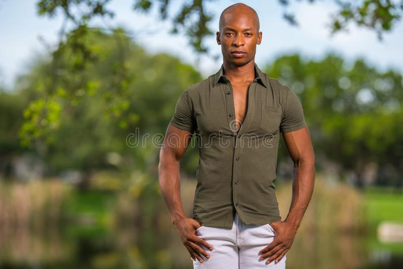 Männliches Modell des Foto-hübschen jungen Afroamerikaners, das mit den Händen in den Taschen aufwirft stockbilder