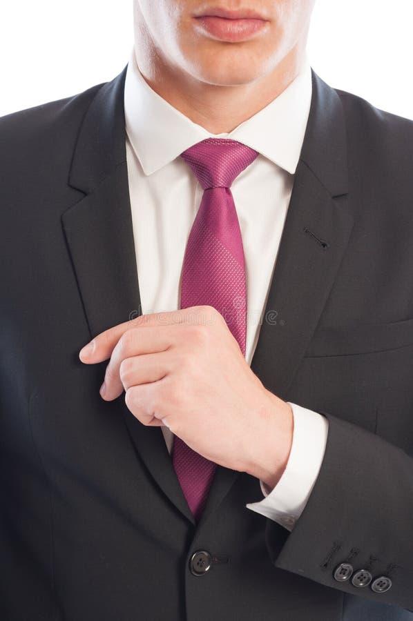 Männliches Modell des modernen Geschäfts, das seins Anzugsjacke regelt stockbilder