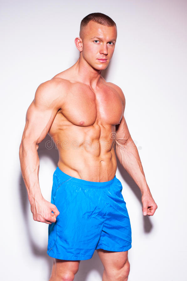 Männliches Modell mit Muskeln, das im Studio aufwirft. stockbild