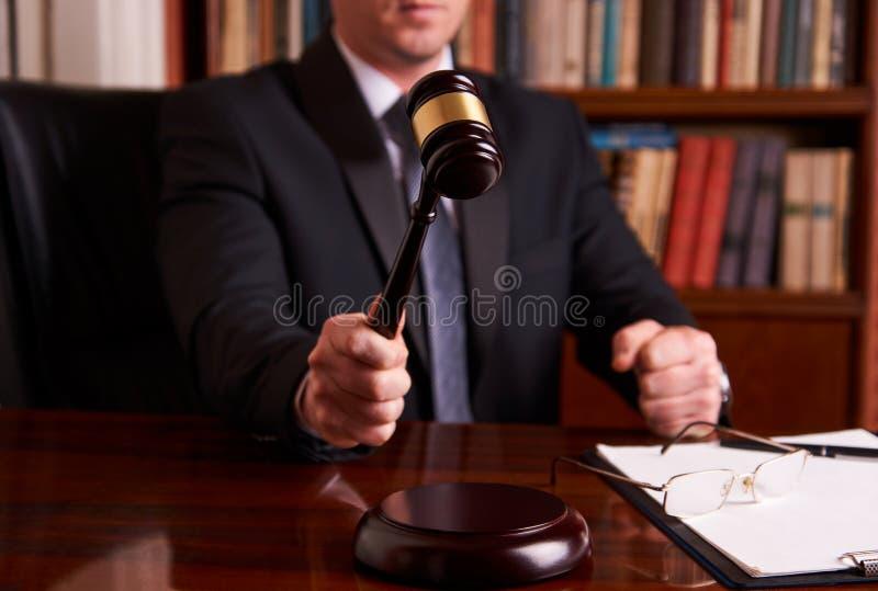 Männliches Rechtsanwalt- oder Richterhand-` s, das den Hammer schlägt stockbild