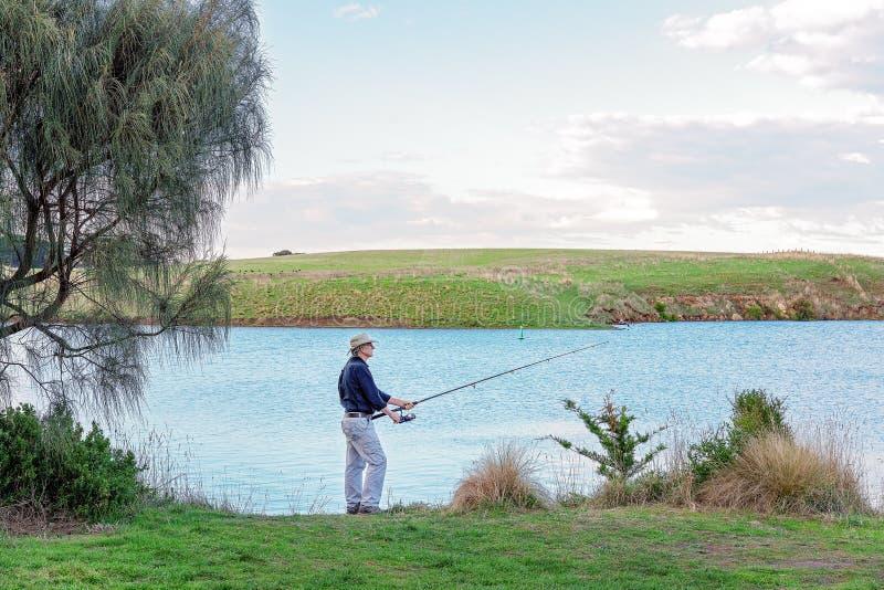Männliches Rentner-Fischen auf einem Fluss stockfotografie