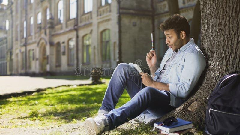 Männliches Sitzen der Mischrasse unter Baum, Schreiben im Sketchbook, innovative Idee lizenzfreies stockfoto