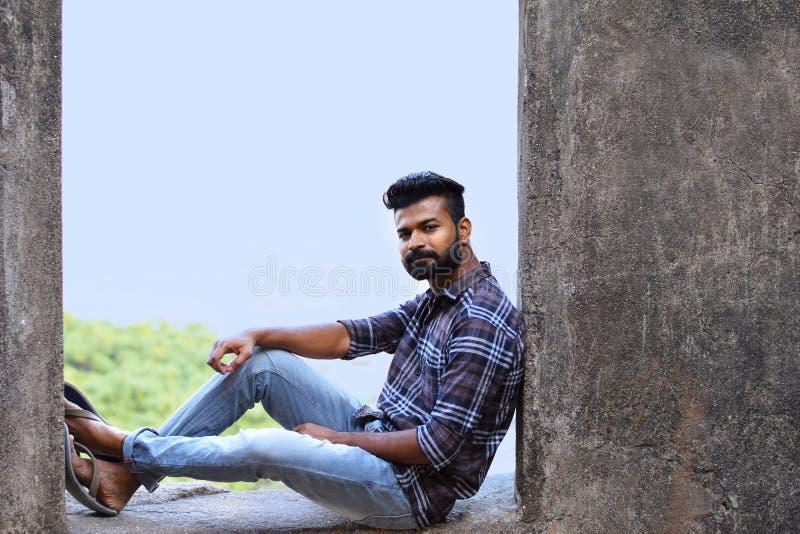 Männliches vorbildliches Sitzen auf einer Felsenleiste, die Kamera, Sions-Fort, Mumbai betrachtet lizenzfreies stockfoto