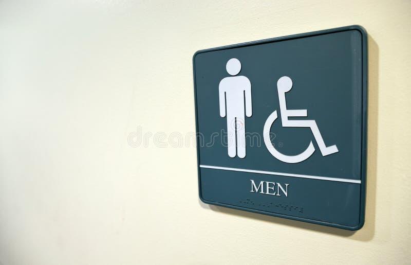 Mäns badrumtecken på den vita väggen med handikappat symbol royaltyfria foton