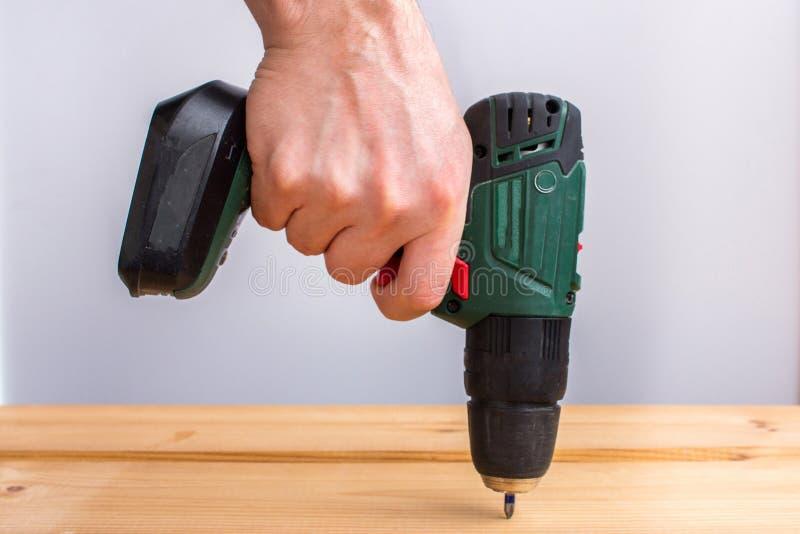 Mäns drillborr för batteri för handinnehav och borra träbrädet royaltyfri bild