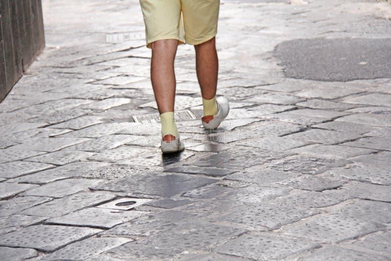 Mäns fot i ljusa skor och gula sockor går vidare vägen Ön av Sicilien, Italien Mäns moment arkivfoto