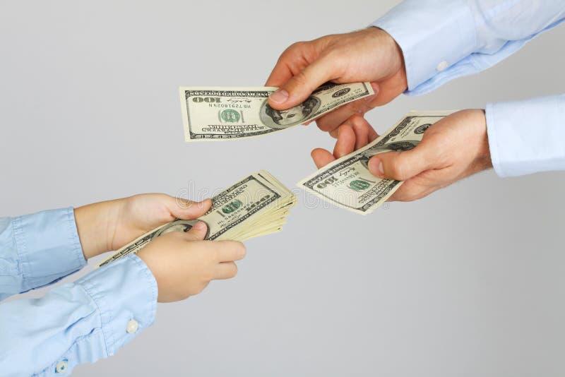Mäns händer ger pengaramerikanen hundra dollarräkningar till pojkehänder Affärsmannen ger pengar till affärspojken Fader och son royaltyfri foto