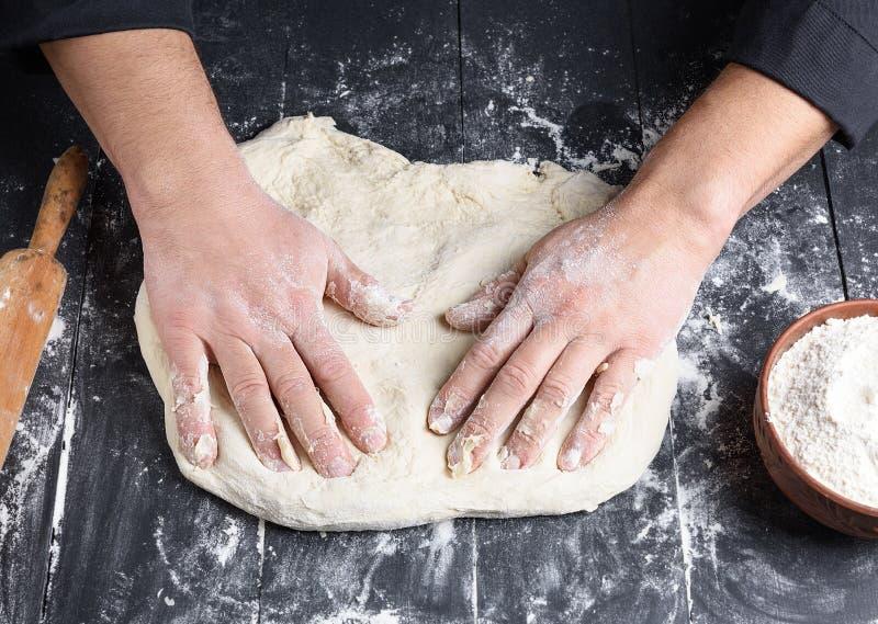 Mäns händer knådar ett runt stycke av deg för framställning av pizza fotografering för bildbyråer