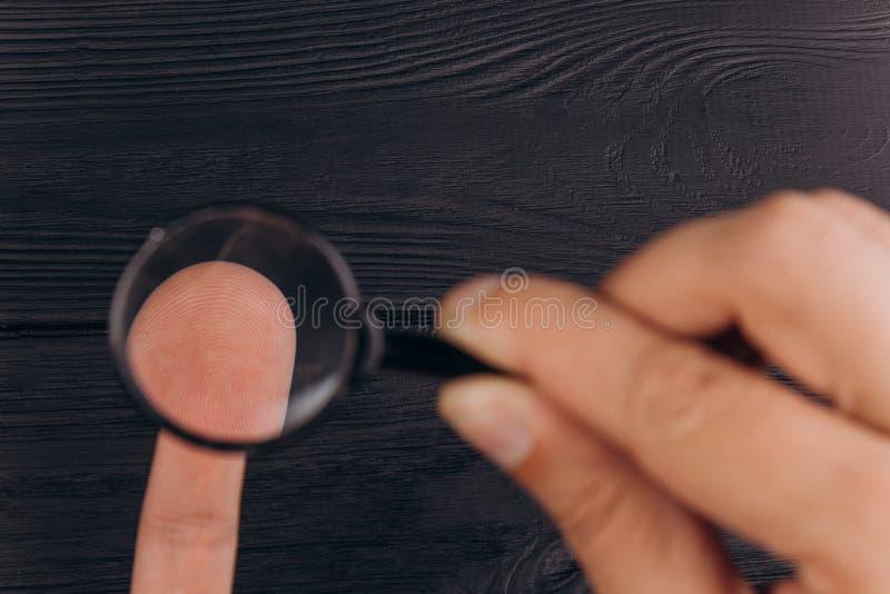 Mäns händer på ett lantligt svart skrivbord som rymmer ett förstoringsglas fingeravtryckundersökning gömma i handflatan clo royaltyfri fotografi