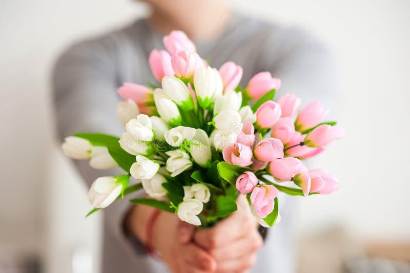 Mäns händer sträcker en bukett av vårblommor Bukett av rosa och vita tulpan closeup och kopieringsutrymme royaltyfri foto