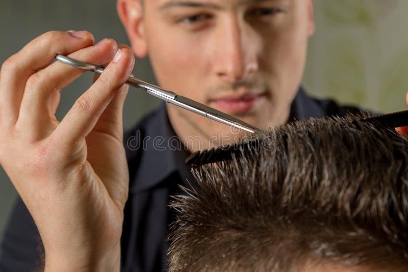 Mäns hårklipp med sax i en skönhetsalong arkivbilder