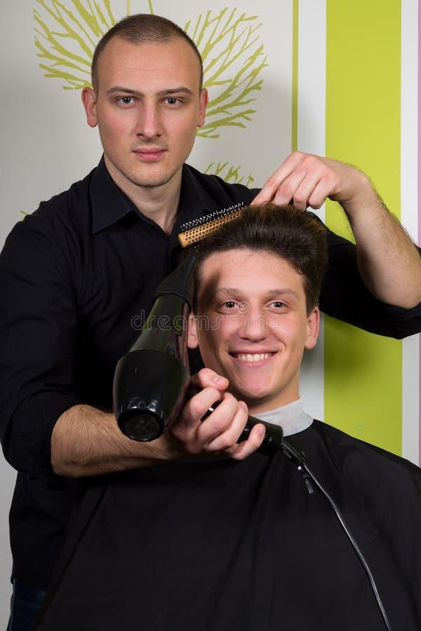 Mäns hairstyling och haircutting med hårclipperen och scissor royaltyfri foto