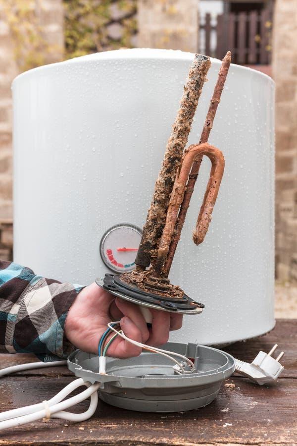 Mäns hand som rymmer uppvärmningbeståndsdelen för behållare för vattenuppvärmning fotografering för bildbyråer