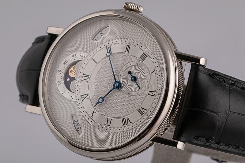 Mäns klocka med chronographen, stoppuren på läderrem med den vita visartavlan, svarta nummer och händer som isoleras på vit bakgr arkivfoto