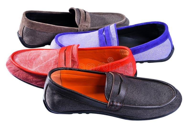 Mäns skor - mång- kulöra mockasin Fyra olika färgskomockasin som isoleras på vit bakgrund arkivbild