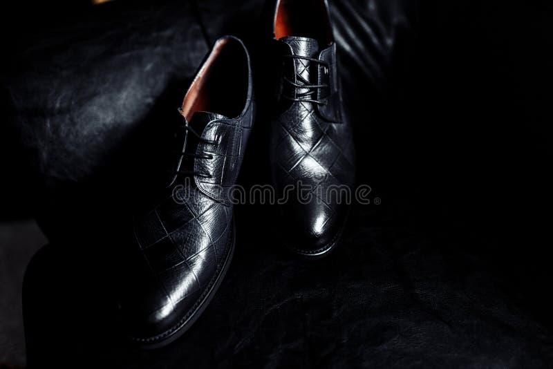 Mäns skor på en mörk bakgrund Stilfulla mäns skor på en tabell på en mörk träbakgrund royaltyfria bilder