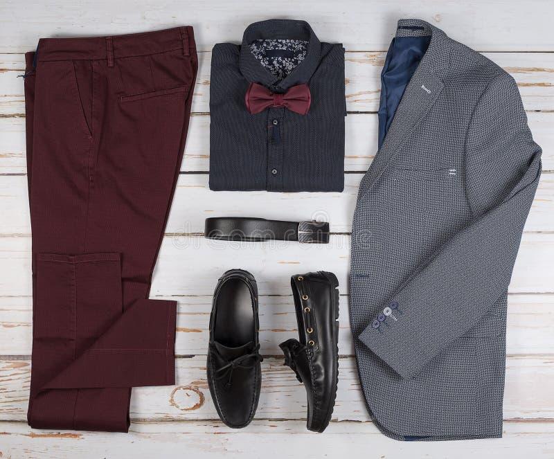 Mäns ställde tillfälliga dräkter in för mankläder med skor, byxa, skjortan och bowtee på träbakgrund, bästa sikt royaltyfri foto