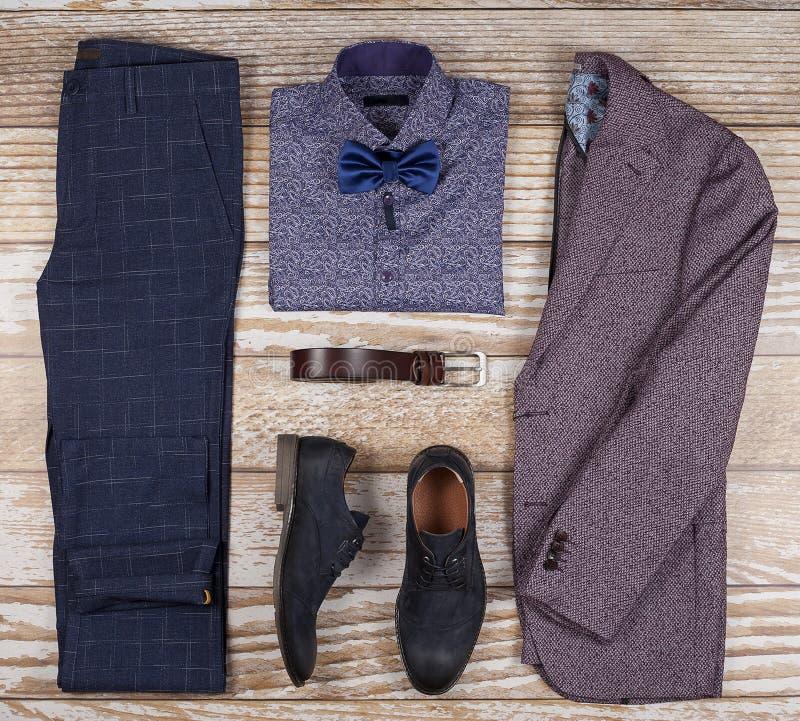Mäns ställde tillfälliga dräkter in för mankläder med skor, byxa, skjortan och bowtee på träbakgrund, bästa sikt royaltyfri bild