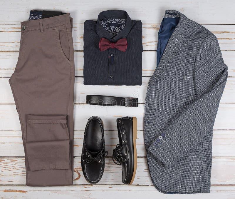 Mäns ställde tillfälliga dräkter in för mankläder med skor, byxa, skjortan och bowtee på träbakgrund, bästa sikt arkivfoto