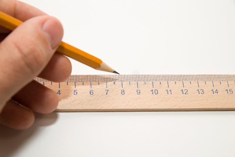 Mäns vänstersidahand som rymmer en blyertspenna på över vit arkivfoto