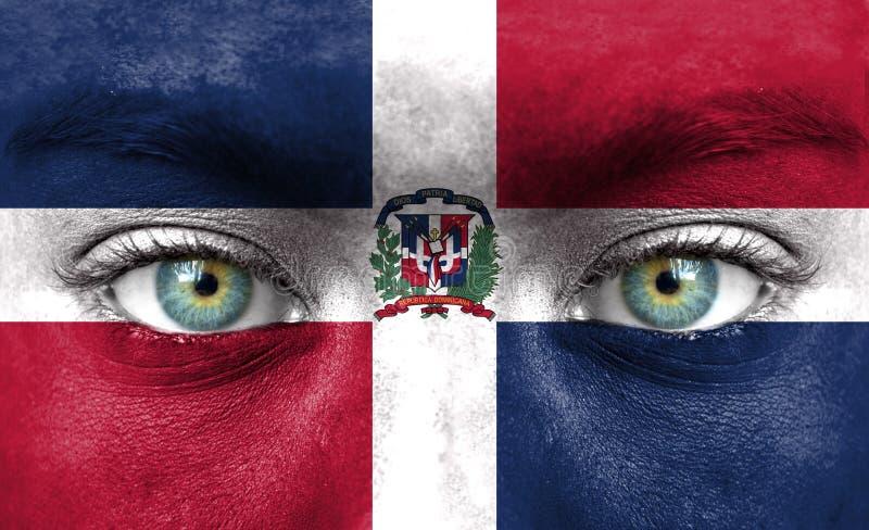 Mänsklig framsida som målas med flaggan av Dominikanska republiken fotografering för bildbyråer