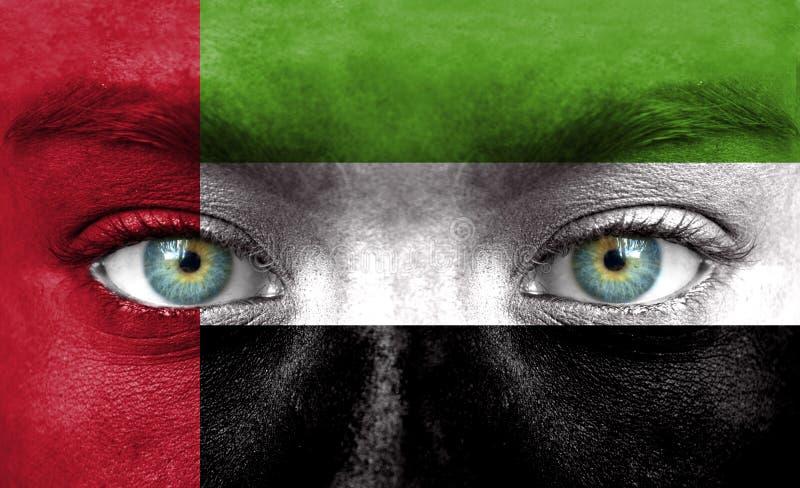 Mänsklig framsida som målas med flaggan av Förenade Arabemiraten royaltyfri foto
