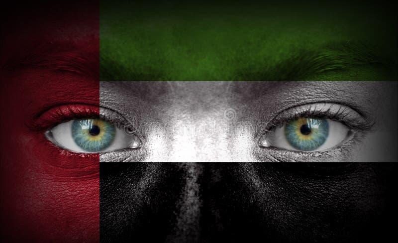 Mänsklig framsida som målas med flaggan av Förenade Arabemiraten arkivfoto