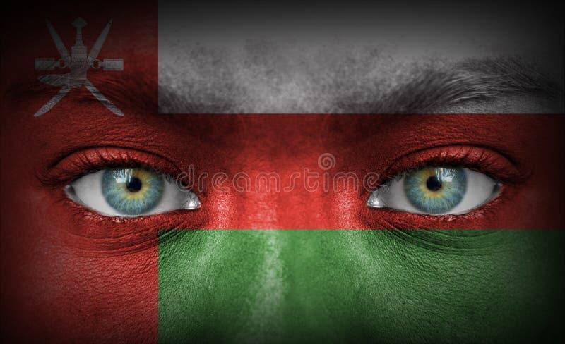 Mänsklig framsida som målas med flaggan av Oman arkivbilder