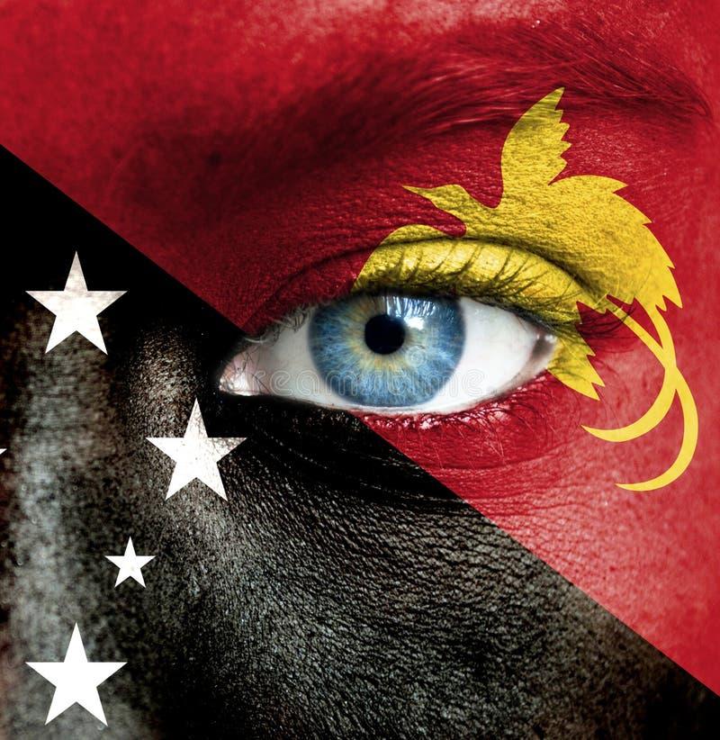 Mänsklig framsida som målas med flaggan av Papua Nya Guinea arkivfoton